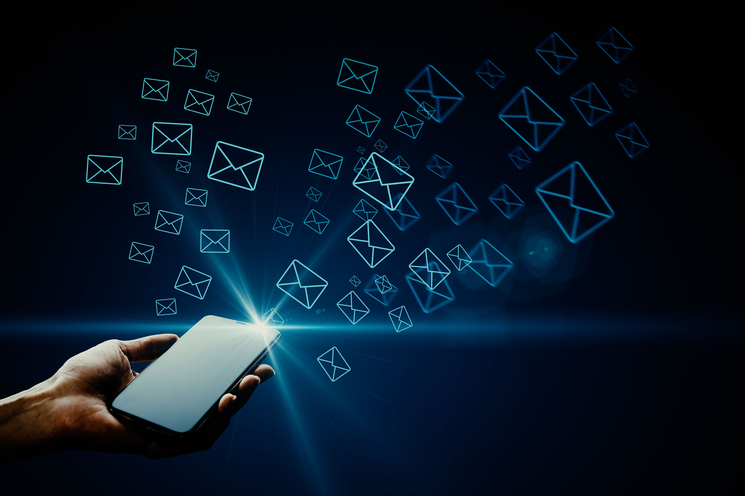 Hand holding smartphone with glowing letter icons. E-mail marketing concept